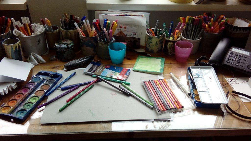 Floras Schreibtisch mit vielen Malsachen: Viele Becher mit Stiften, Wasserfarbkästen, Papier, Filzstifte in einer Packung und verstreut Holzmalstifte. An der Seite ein schwarzes Telefon mit Schnur.