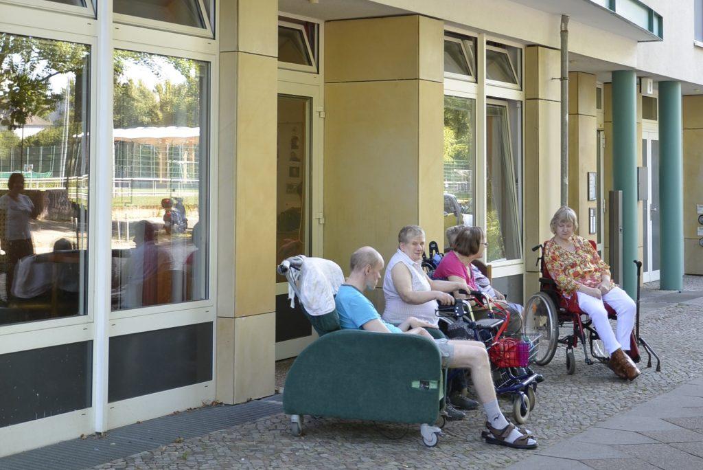 Vier Personen sind auf dem Gehweg vor dem Haus ZOAR.  Drei benutzen Rollstühle, eine Frau benutzt einen Rollator.
