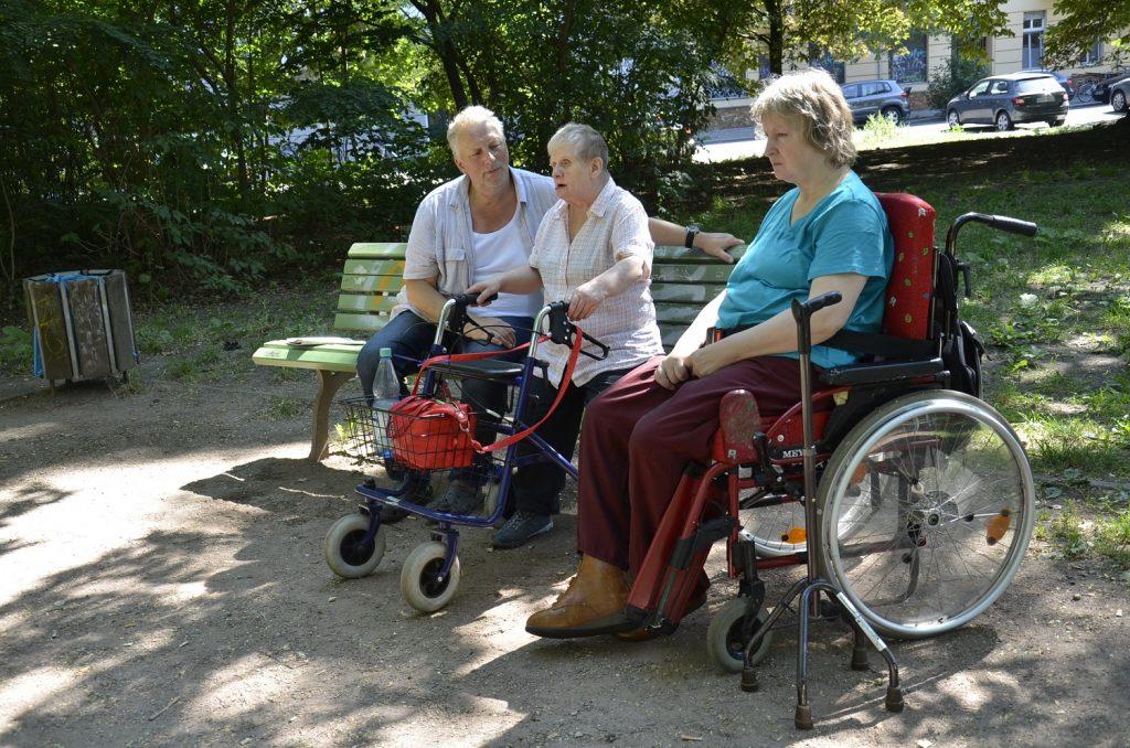 Detlef und Dagmar sitzen draußen im Grünen auf einer Parkbank. Dagmar hält sich an ihrem Rollator fest. Neben Dagmar sitzt Evelyn in ihrem Rollstuhl.