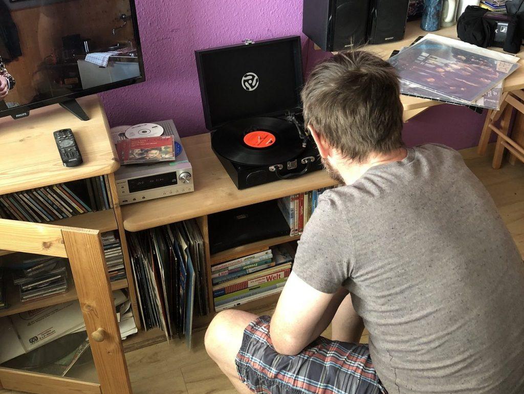 Uli in seinem Zimmer. Er hockt vor einem niedrigen Regal mit einem Plattenspieler und anderen Geräten. Er ist von hinten zu sehen. Die Wand dahinter ist lila.