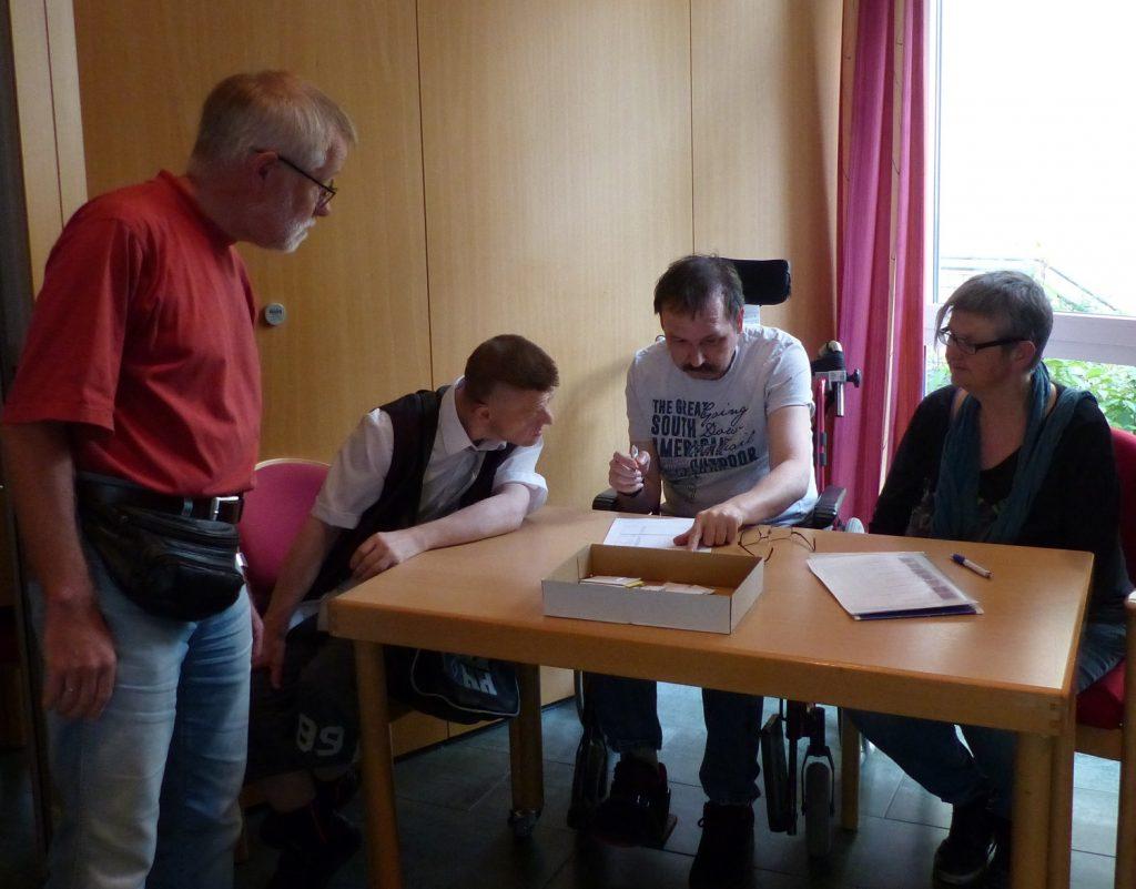 Drei Menschen sitzen an einem Tisch. Ein Mann in der Mitte hat einen Stift in der Hand und einen Zettel vor sich. Neben dem Tisch steht ein weiterer Mann. Alle vier schauen auf den Zettel, den der Mann in der Mitte vor sich hat.