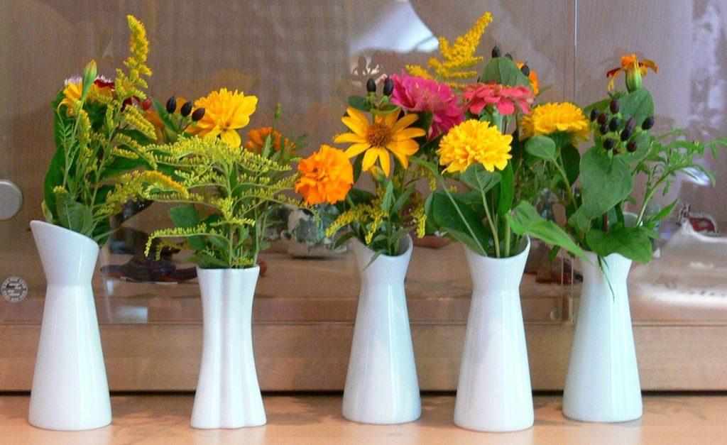 Fünf weiße Blumenvasen mit kleinen Blumensträußen stehen nebeneinander. Die Blumen sind überwiegend gelb, orange und rot.