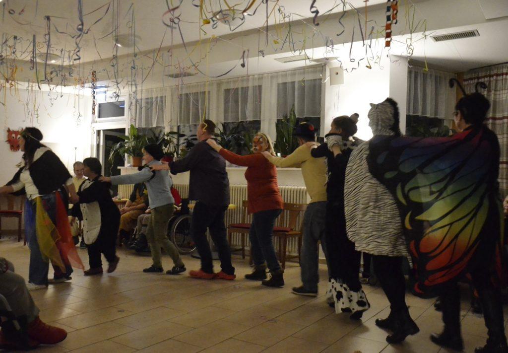 Eine Gruppe von Menschen macht eine Polonaise. Die Menschen sind zum Teil verkleidet oder tragen Masken oder beides. Von der Decke hängen Luftschlangen.