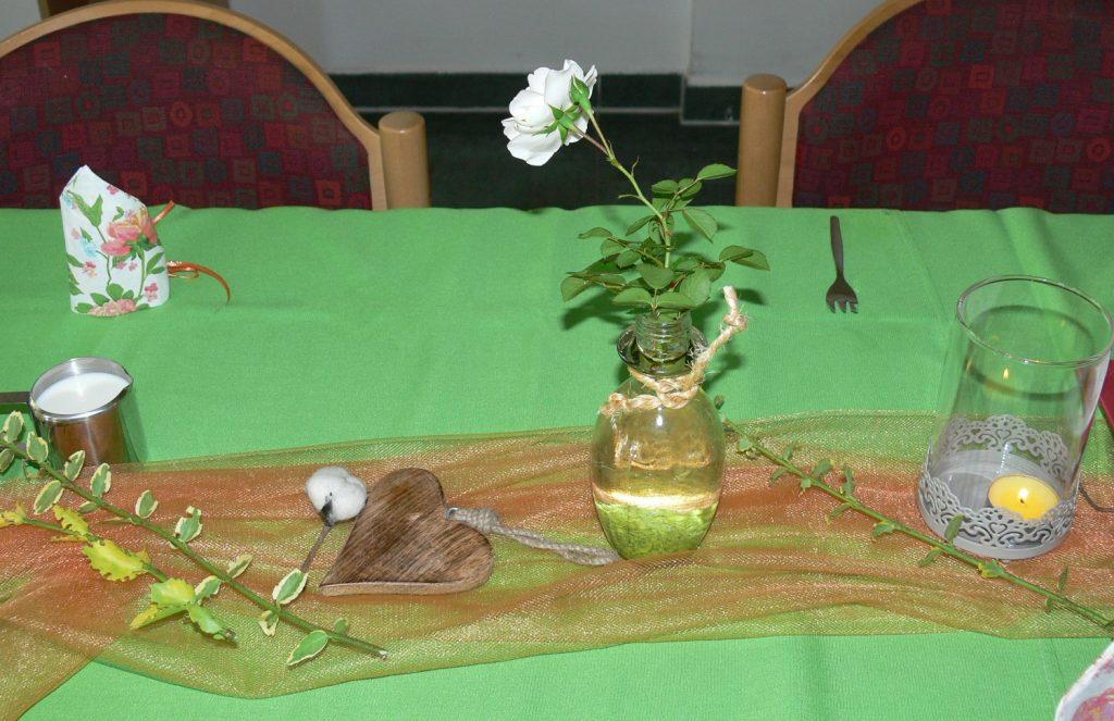 Ein Teil von einem langen Tisch mit einer grünen Tischdecke. In der Mitte Dekoration: ein Herz aus Holz, eine Blumenvase mit einer weißen Rose, ein brennendes Teelicht in einem Glas, alles auf einem langen Stück Stoff. Der Stoff ist halb durchsichtig und glänzt.