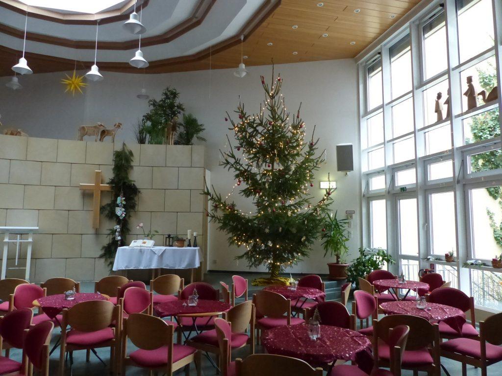 Ein großer heller Saal mit einer hohen Decke. Auf der rechten Seite Fenster bis an die Decke. Im Raum stehen Stühle mit roten Polstern an mehreren runden Tischen mit roten Tischdecken. Im Hintergrund eine Wand mit einem Kreuz. Daneben ein großer beleuchteter Weihnachtsbaum.