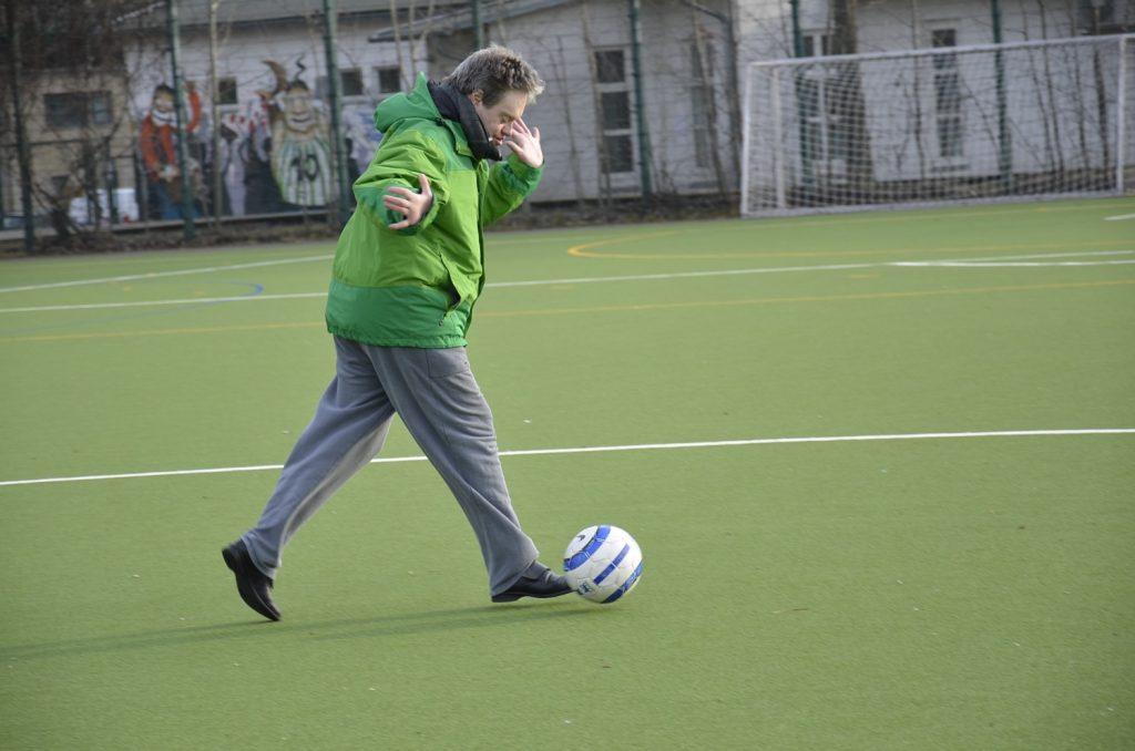 Harald läuft über ein Fußballfeld und kickt dabei einen Ball. Im Hintergrund ein Fußballtor.