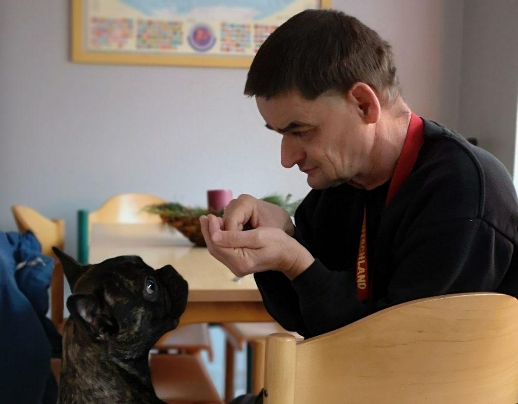 Matthias und ein kleiner schwarzer Hund schauen einander an. Matthias sitzt auf einem Stuhl neben einem Tisch und füttert den Hund.