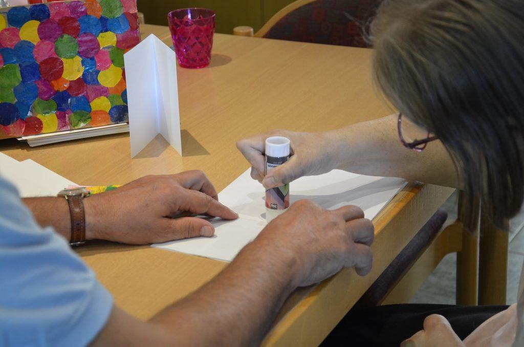Eine Teilnehmerin benutzt einen Klebestift auf einem Blatt Papier. Ein Mann hält das Papier mit beiden Händen fest. Es sind nur seine Arme zu sehen. Auch von der Frau sieht man nur einen Teil. Ihr Gesicht ist nicht zu sehen. Links ist ein Bild mit leuchtend bunten Punkten aus Drachenpapier zu sehen.