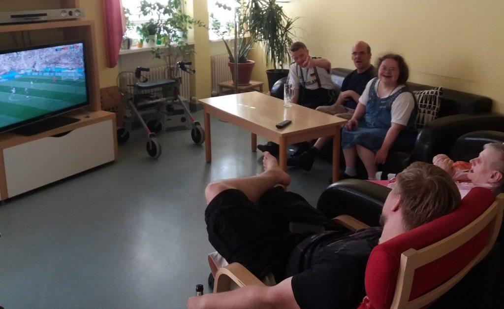 Der Gemeinschaftsraum der WG 6. Fünf Menschen sitzen auf einem Sofa und auf Sesseln vor einem Fernseher. Sie schauen gemeinsam Fußball.