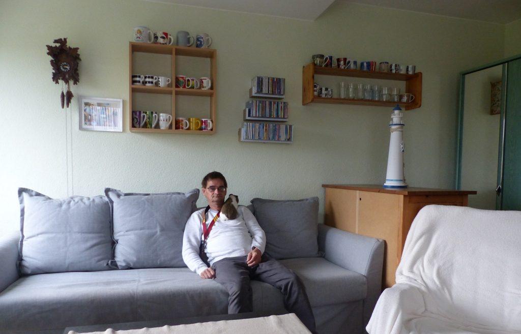 Matthias sitzt auf einem großen hellgrauen Sofa und schaut in die Kamera. Auf seiner rechten Schulter liegt ein braun-weißes Meerschweinchen. An der Wand im Hintergrund gibt es Regale mit Tassen und CDs und eine Kuckucksuhr.
