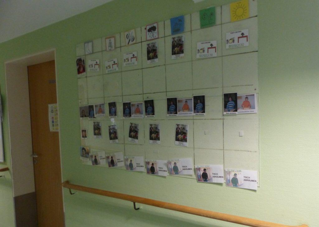 Ein Wochenplan an einer Wand im Flur der WG 6, unter anderem mit Piktogrammen von den Wochentagen und Fotos von Mitarbeitenden.