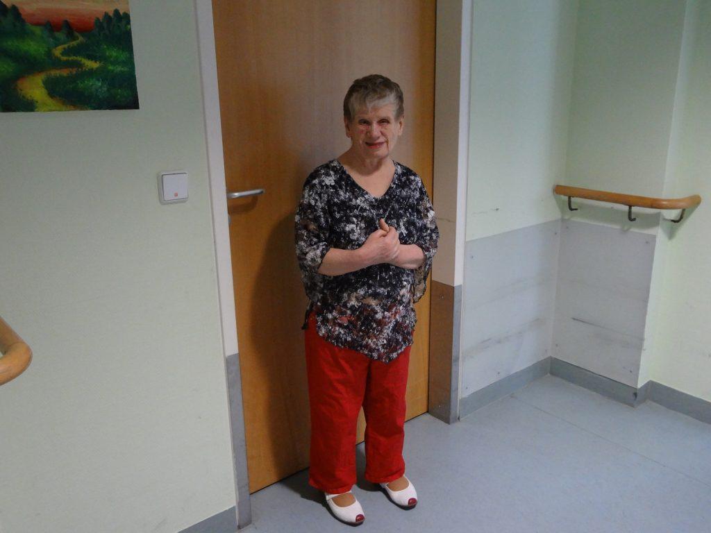 Dagmar in einer roten Hose vor ihrer Zimmertür. Rechts an der Wand sind Handläufe.