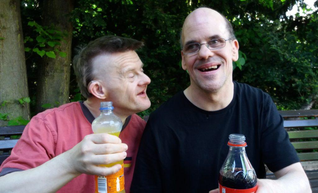 Thilo und Christian sitzen draußen auf einer Parkbank und lachen. Thilo hat sich Christian zugewandt. Beide haben je eine Getränkeflasche in der Hand. Im Hintergrund Bäume und Büsche.