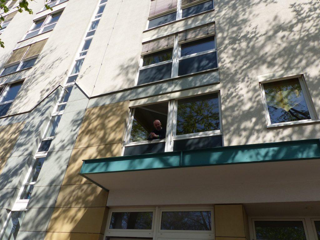 Blick von unten auf die Fassade vom Haus ZOAR. Lutz schaut aus einem Fenster im ersten Stock.