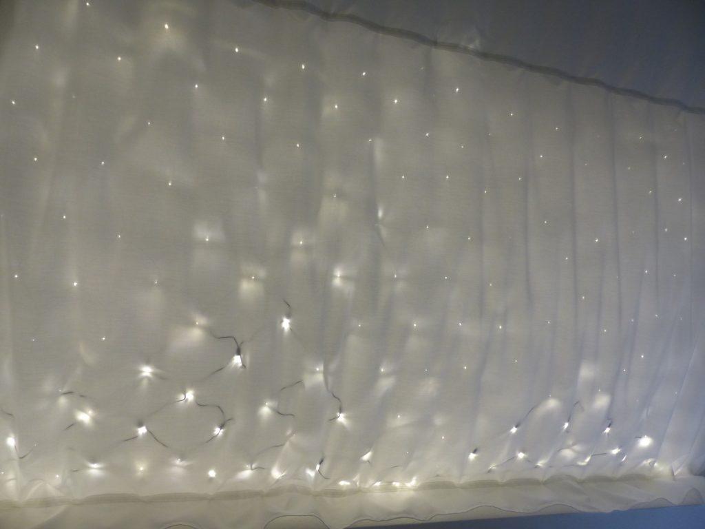 Ein Lichternetz über weißem Stoff.