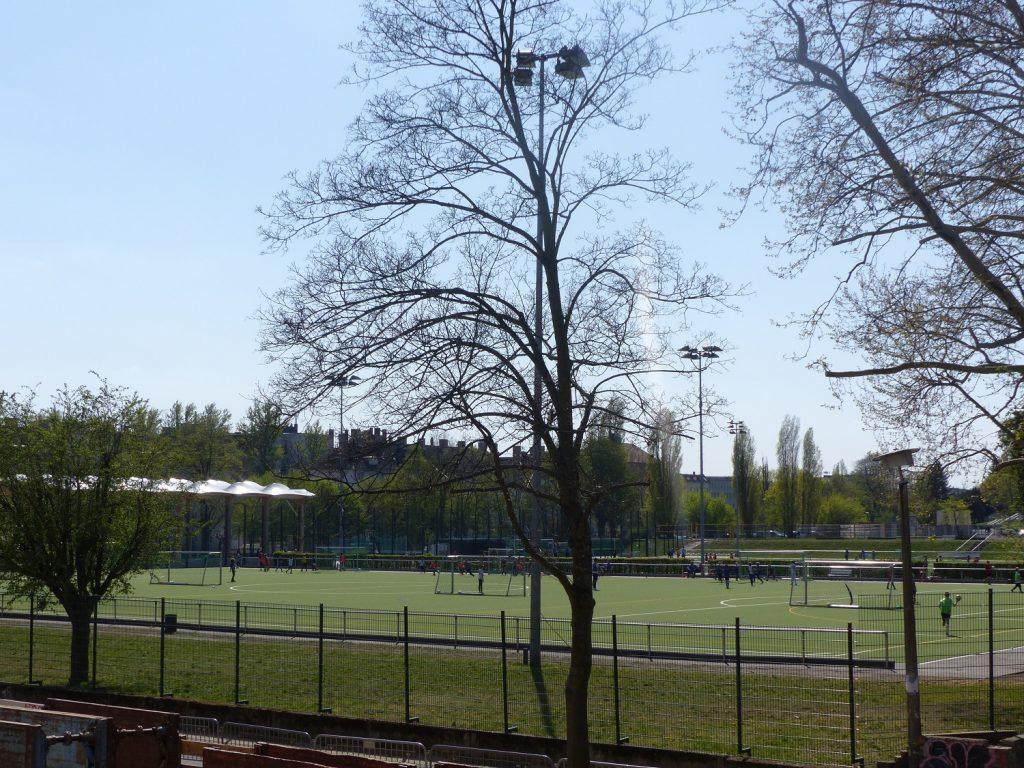 Blick auf einen Fußballplatz im Ludwig-Jahn-Sportpark gegenüber vom Haus ZOAR. Die Sonne scheint und es wird gerade trainiert.