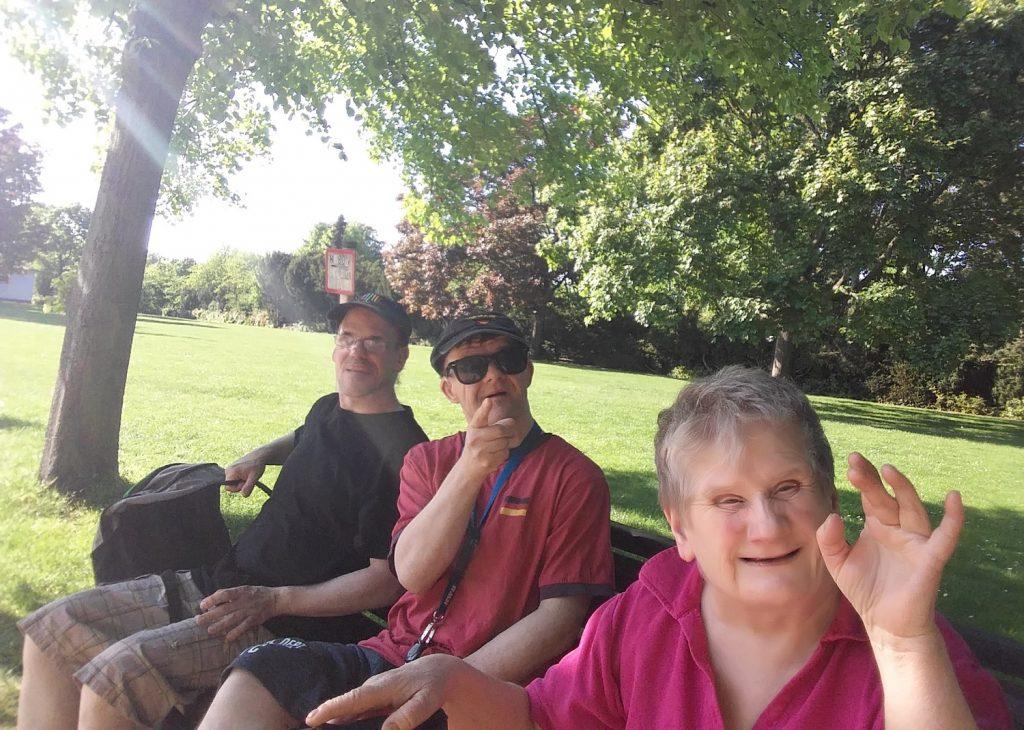 Christian, Thilo und Dagmar sitzen auf einer Bank in einem Park. Sie tragen Sommerkleidung, die Sonne scheint.
