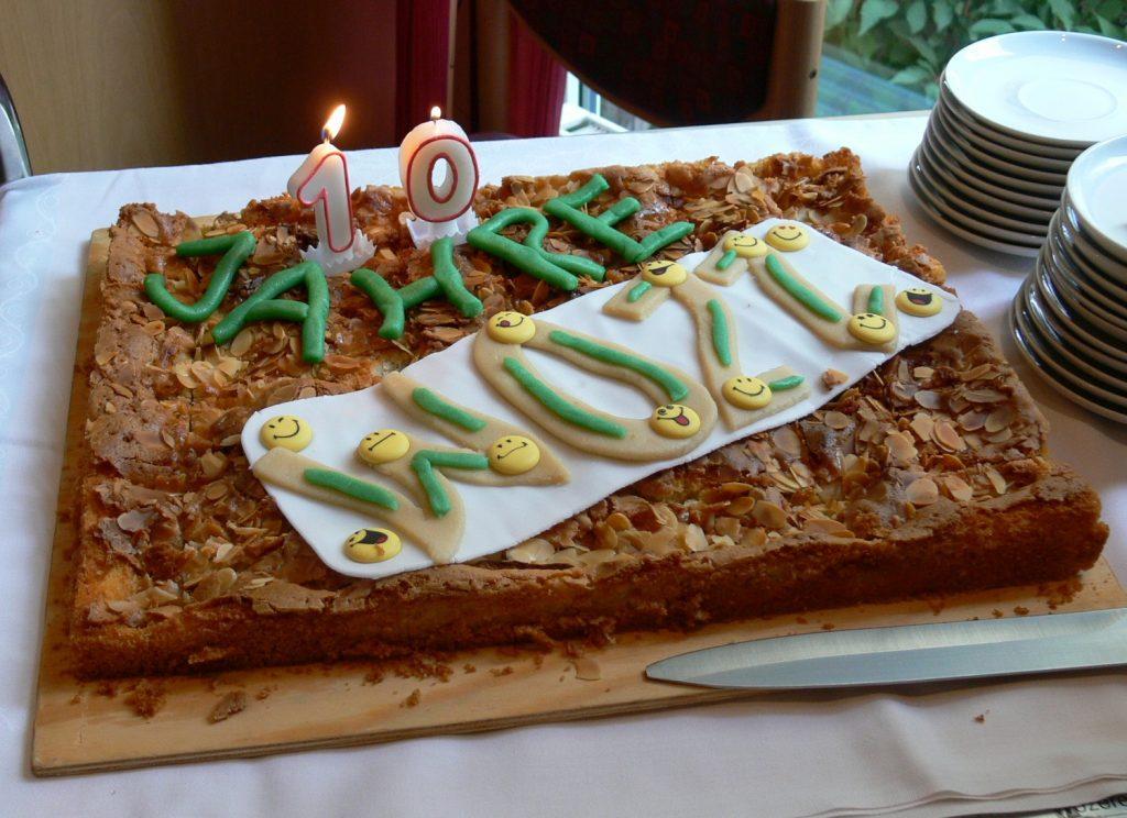 Ein rechteckiger Kuchen mit Mandeln. Auf dem Kuchen: Zwei brennende Kerzen in Form einer Eins und einer Null bilden die Zahl 10. Darunter steht in einer Schrift aus Marzipan: Jahre ZOAR.