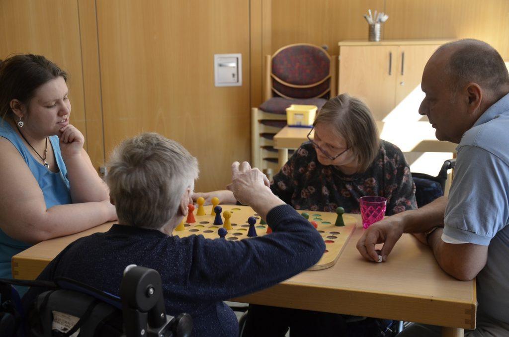 Drei Teilnehmerinnen der WoZerei und ein Mitarbeiter sitzen um einen Tisch und spielen Mensch ärgere Dich nicht mit einem großen Spielbrett aus Holz.
