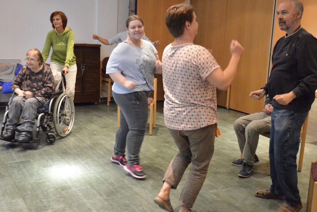 Sechs tanzende Menschen, eine davon im Rollstuhl.