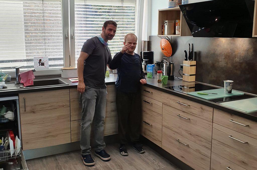 Liron und Robert stehen vor einer Arbeitsplatte in der Küche der WG 4 und schauen in die Kamera. Robert zeigt mit dem Finger in Richtung Kamera. Im Hintergrund befindet sich ein großes Fenster. Links ist eine geöffnete Spülmaschine zum Teil zu sehen.