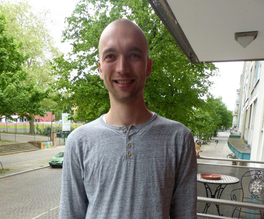 Stefan steht auf einem Balkon im ersten Stock und lächelt in die Kamera. Im Hintergrund ist die Cantianstraße zu sehen mit grünen Bäumen und Autos.
