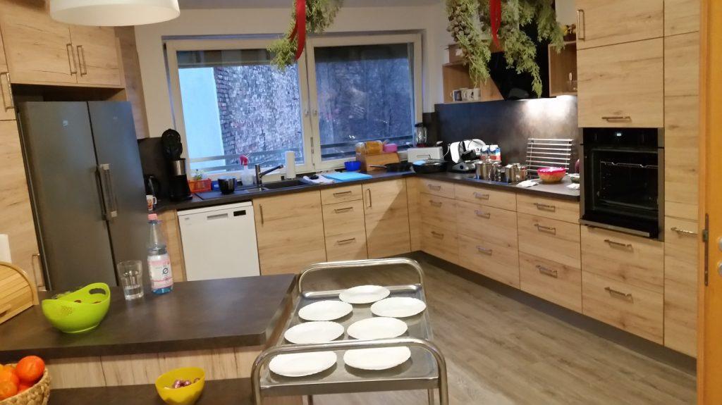 Ein großer Raum mit einer Einbauküche in Holz-Optik. Im Hintergrund ein großes Fenster. Im Vordergrund ein Servierwagen mit Tellern.