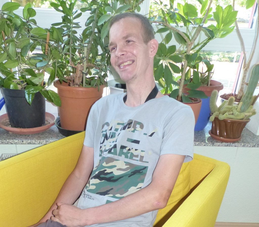 Christian sitzt in einem gelben Sessel, er lächelt. Er trägt ein kurzärmeliges T-Shirt. Im Hintergrund grüne Topfpflanzen auf einem Fenstersims.