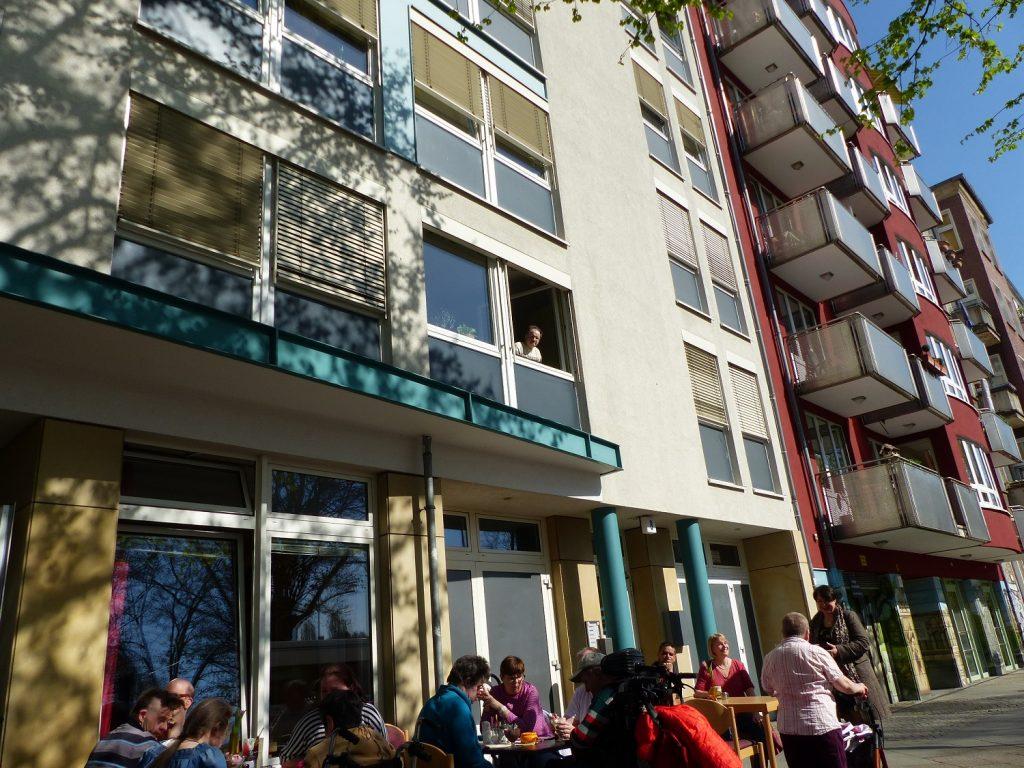 Mehrere Leute sitzen draußen vor dem Haus ZOAR auf dem breiten Gehweg an kleinen Tischen bei Kaffee und Kuchen. Die Sonne scheint.