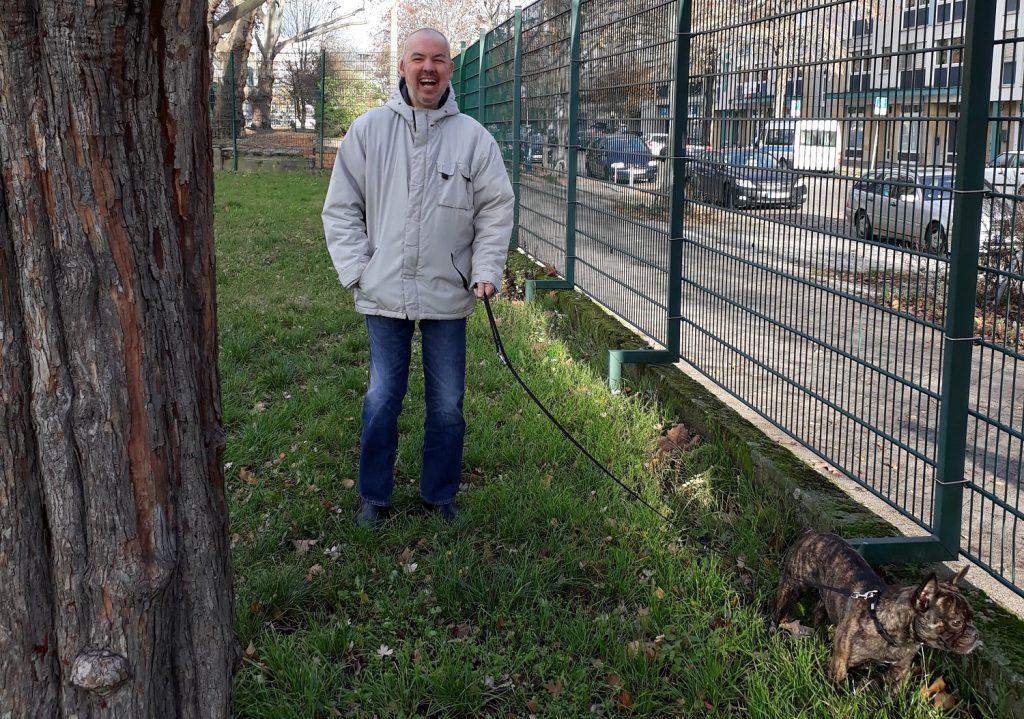Lutz führt Hunde Locke an einer Leine aus. Draußen auf einer Wiese direkt neben der Straße. Zwischen der Straße auf der linken Seite und der Wiese ist ein hoher Zaun. Lutz trägt eine hellgraue Jacke und lacht in die Kamera.