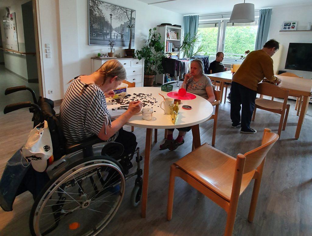 Ein großer, gemütlicher Raum. Im Vordergrund sitzen sich Annemarie und Annette an einem runden Tisch gegenüber, Annemarie im Rollstuhl. Sie ist mit Basteln beschäftigt. Im Hintergrund ein weiterer, großer Tisch. An diesem Tisch steht Detlef mit dem Rücken zur Kamera. Robert sitzt an diesem Tisch direkt neben einem Fenster. Links ist die offene Tür zum Flur zu sehen.