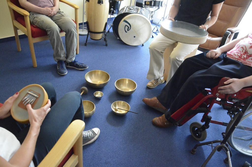Vier Menschen sitzen auf Stühlen im Kreis. Kopf und Schultern der Menschen sind nicht zu sehen. In der Mitte liegen mehrere Klangschalen. Zwei Personen haben Instrumente auf dem Schoß. Im Hintergrund ein Schlagzeug.
