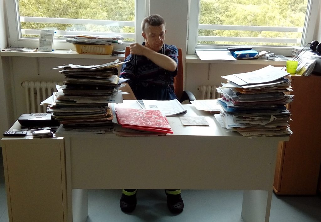 Der Schreibtisch ist im Vordergrund. Dahinter sitzt Thilo mit dem Rücken zu zwei großen Fenstern, die den Blick auf grüne Bäume freigeben.