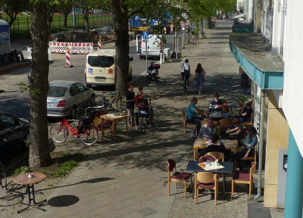 Blick von einem Balkon auf den Gehweg vor dem Haus ZOAR. Dort stehen Tische und Stühle, an denen zum Teil Menschen sitzen. Die Sonne scheint.