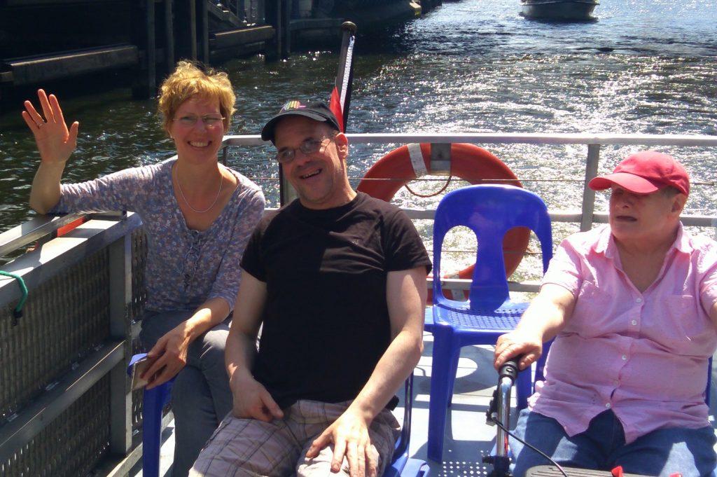 Kathrin, Christian und Dagmar sitzen auf blauen Plastikstühlen an Deck eines Ausflugsschiffs. Im Hintergrund ist ein Rettungsring zu sehen, dahinter Wasser. Kathrin winkt in die Kamera. Christian und Dagmar tragen Schirmmützen. Die Sonne scheint.