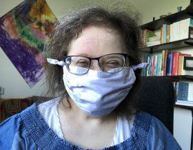Kopf und Schultern von Flora. Sie trägt eine Brille und einen Mund-Nasen-Schutz