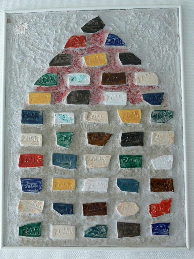 Unregelmäßig geformte Tonziegel in bunten Farben sind zu einem Haus angeordnet. Auf den Ziegeln ist das Wort ZOAR eingebrannt. Der Hintergrund ist weiß.