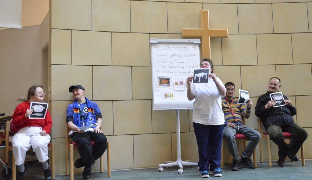 Fünf Bewohnerinnen und Bewohner stellen eine Bewohnerversammlung nach. Vier sitzen auf Stühlen. Eine Frau steht neben einem Flipchart in der Mitte. Sie und drei der anderen halten Blätter mit unterschiedlichen Symbolen hoch. Die Szene wird im Gemeindesaal der Zoar-Kirche aufgeführt.