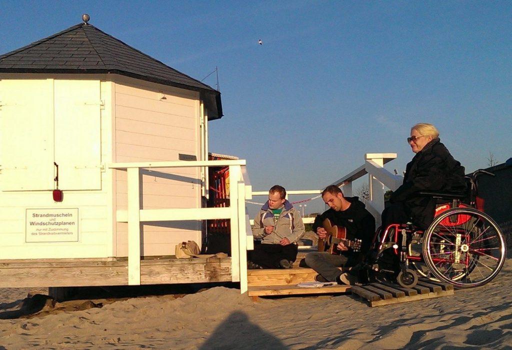 Links ein kleines weißes Holzhaus mit einer Holz-Terrasse am Strand. Robert und David sitzen auf der Stufe zur Terrasse, Annemarie in ihrem Rollstuhl daneben. David spielt Gitarre. Im Hintergrund blauer Himmel. Im Vordergrund Sand.
