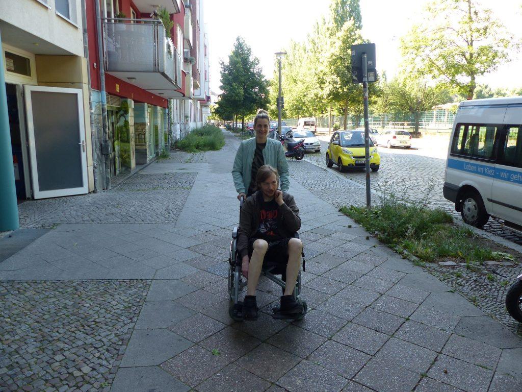 Stephen in einem Rollstuhl auf dem Gehweg vor dem Haus ZOAR. Judith steht hinter ihm. Rechts ist die Cantianstraße zu sehen und ein Teil des hauseigenen Kleinbusses.