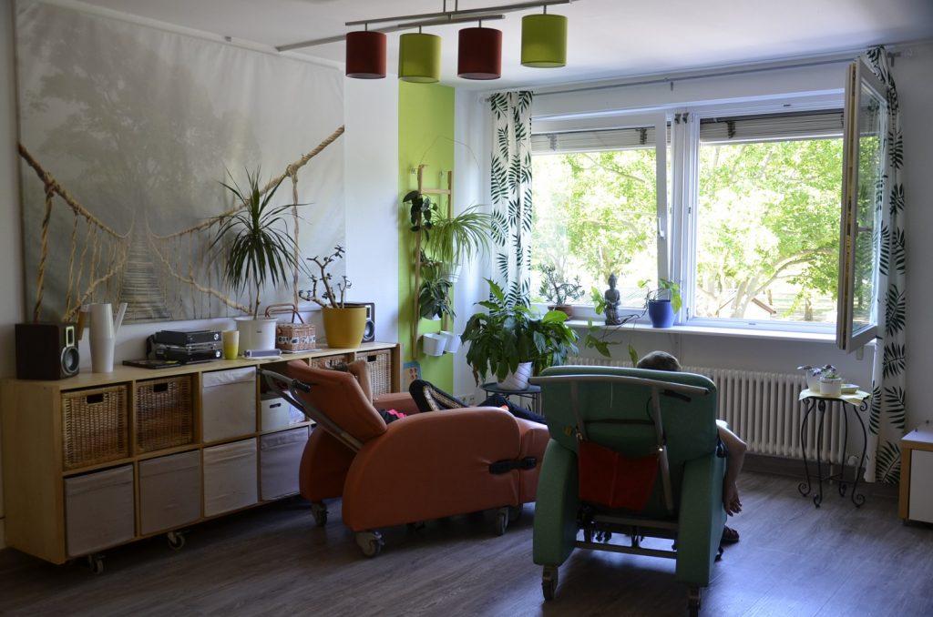 Ein Raum mit Pflanzen, einem großen Bild an der Wand und Holzmöbeln. Zwei Menschen sitzen in großen Sesseln mit Rollen und schauen durch ein offenes Fenster auf einen grünen Baum. Die Menschen sind von hinten zu sehen.