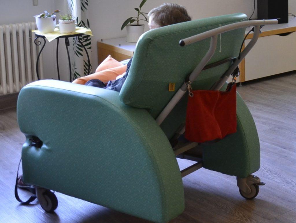 Großaufnahme  eines Huntington-Sessels. Das ist ein großer gepolsteter Rollstuhl. Eine Frau sitzt darin. Sie ist von hinten zu sehen. Hinten am Sessel hängt eine rote Tasche.