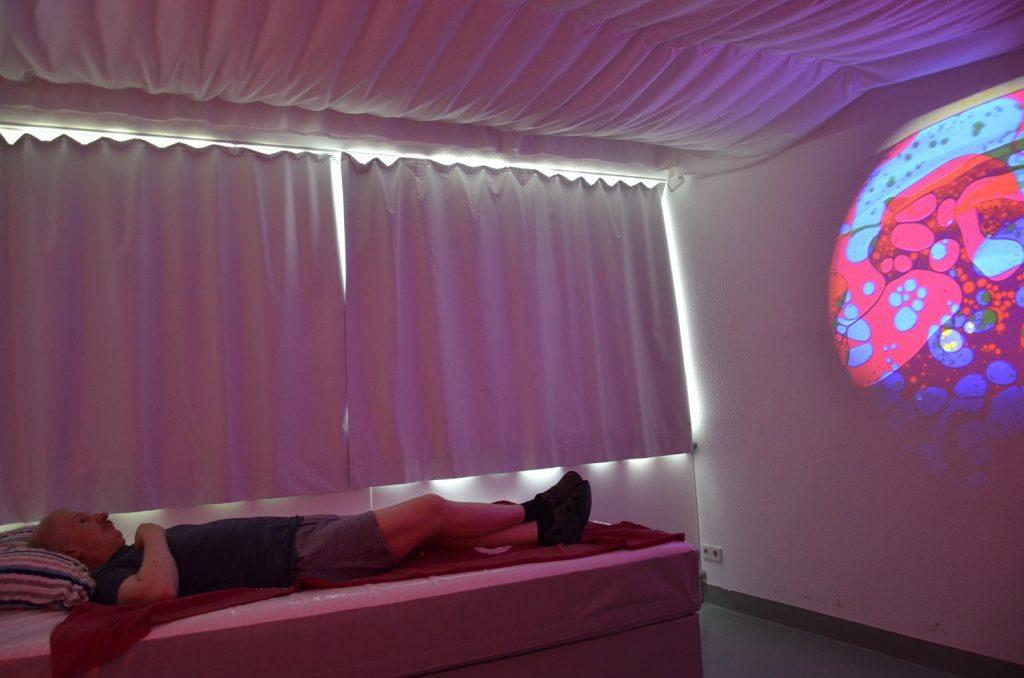 Christian liegt auf dem Wasserbett und blickt auf eine bunte Licht-Projektion an der Wand. Das Bett befindet sich vor einem Fenster. Die weißen Vorhänge sind zugezogen. An der Decke hängt ebenfalls weißer Stoff.
