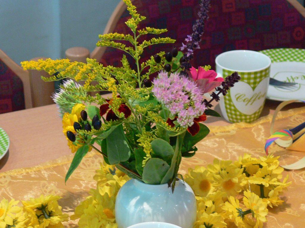 Ein bunter Blumenstrauß in einer weißen Vase auf einem Tisch. Ein Tischläufer mit Blumendeko. Im Hintergrund rechts sind eine Tasse und ein Kuchenteller zu sehen.