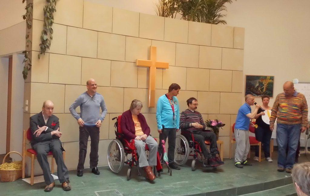 Sieben Bewohnerinnen und Bewohner und ein Mitarbeiter stehen oder sitzen nebeneinander auf dem Podium in der Kapelle der Kirchengemeinde Zoar. Ein Bewohner spricht in ein Mikrophon.