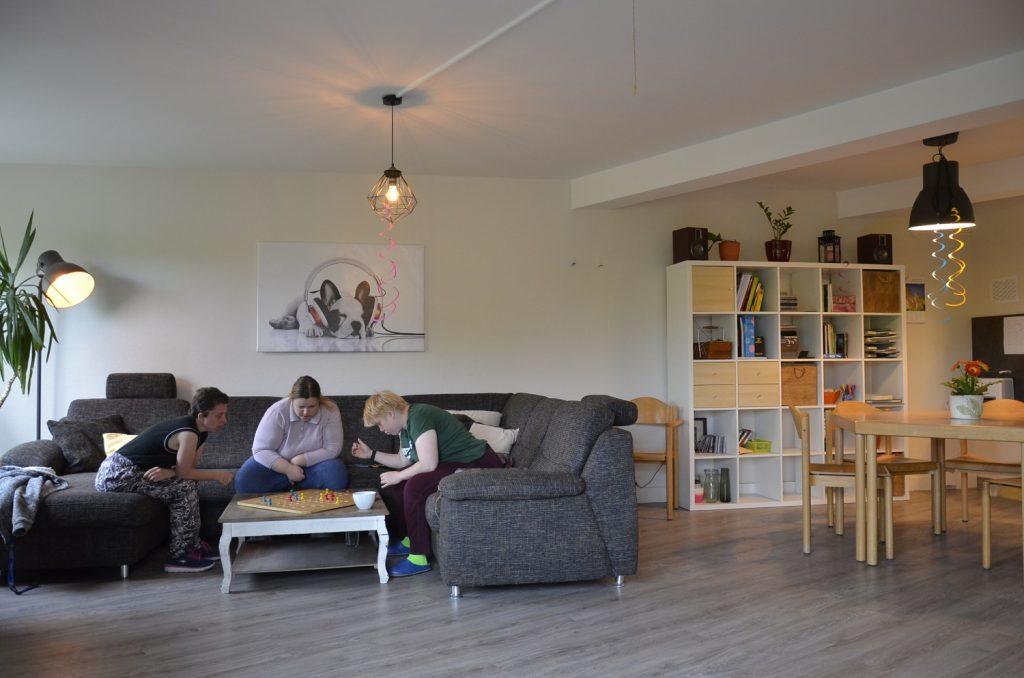 Ein großer, gemütlicher Raum mit einer dunkelgrauen Sofakombination auf der linken Seite. Dort sitzen Tanja, Patricia und Christine über ein Mensch ärgere Dich nicht Brett gebeugt. Christine würfelt gerade. Rechts im Bild befindet sich ein Esstisch mit Stühlen, dahinter ist ein hohes, weißes Regal.