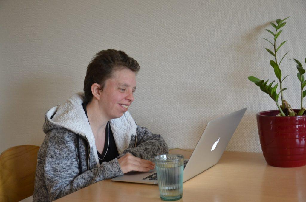 Tanja an einem Tisch vor einem aufgeklappten Notebook-Computer. Sie blickt auf den Bildschirm vom Computer. Auf dem Tisch stehen noch ein gefülltes Wasserglas und eine Pflanze.