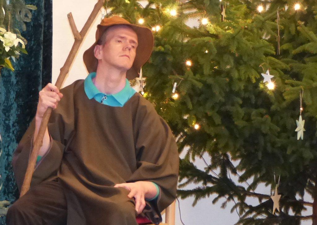 Henrik als Hirte verkleidet. Er trägt eine braune Kutte und auf dem Kopf einen braunen Schlapphut, in der rechten Hand hält er einen Hirtenstab. Er sitzt auf einem Stuhl, rechts im Bild sind einige Äste eines geschmückten und beleuchteten Weihnachtsbaums zu sehen.