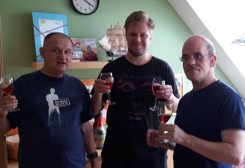 Drei Männer mit Weingläsern stehen nebeneinander in einem Zimmer und schauen in die Kamera. Im Hintergrund eine grüne Wand mit einem Regal.