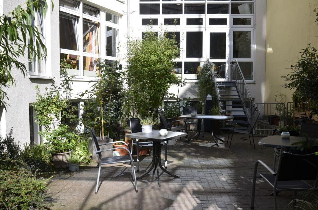 Ein kleiner Hinterhof mit Gartenstühlen und -tischen. Am Rand gibt es Pflanzen, größere und kleinere, in Töpfen und Beeten. Im Hintergrund führt eine Treppe zur Kapelle der Kirchengemeinde Zoar.